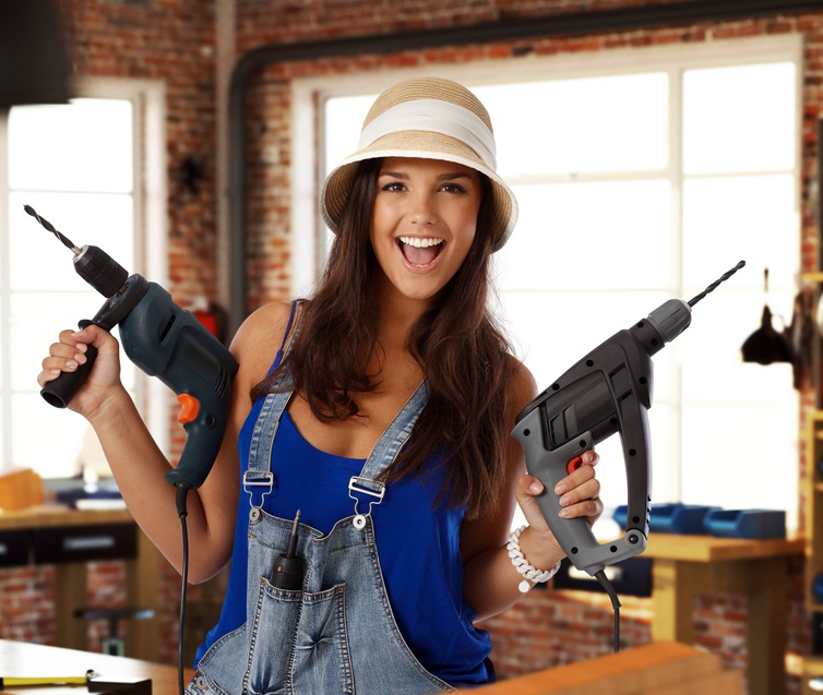 Happy young woman holding power drill at workshop